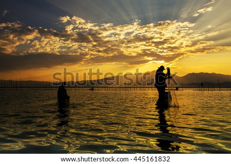 Silhouettes of the traditional fishermen throwing fishing net during sunrise, Thailand - stock photo