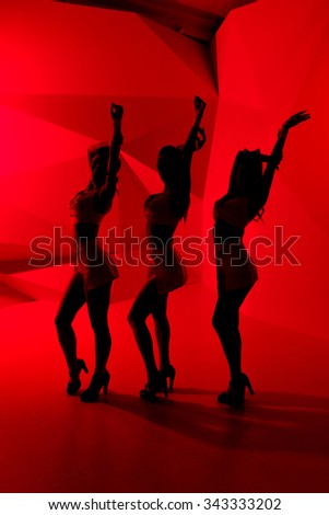 Silhouettes of three sexy posing girls