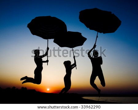 Silhouettes of three young girls with umbrellas jumping in the air on the beach