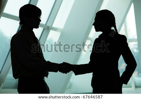 Silhouettes of two business partners handshaking and greeting each other - stock photo