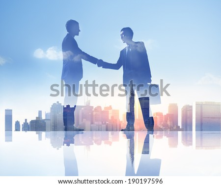 Silhouettes of Two Businessmen Having a Handshake - stock photo