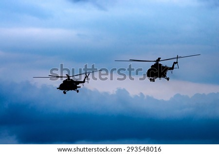 silhouettes of two helicopters flying