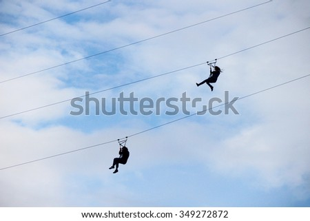 Silhouettes of two people coming down the cable tramway on a background of blue sky in the clouds - stock photo