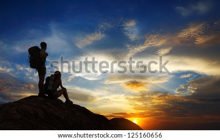 Silhouettes of two tourists with backpacks relaxing on top of a mountain and enjoying sunset view - stock photo