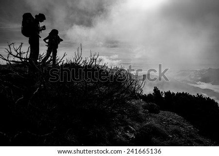 Silhouettes of two women with backpacks on an autumn mountain hike - stock photo