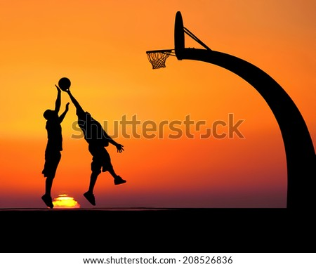 Silhouettes of two young men playing basketball in front of a dramatic sunset - stock photo