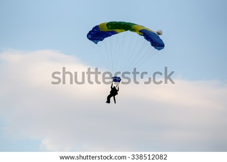 silhouettes of unidentified skydivers parachutist on blue sky on sunset