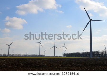 Silhouettes of wind farms on flat plough-land