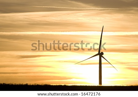 Silhouettes of wind turbines on sunset sky background