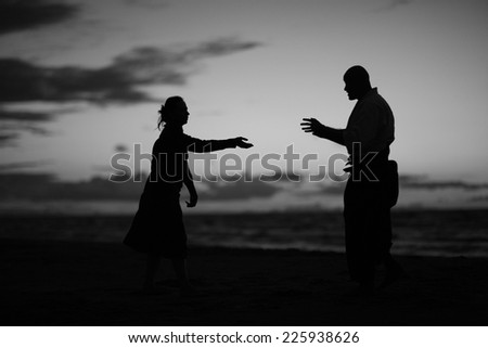 Silhouettes of woman and man stretching hands to each other,monochrome - stock photo