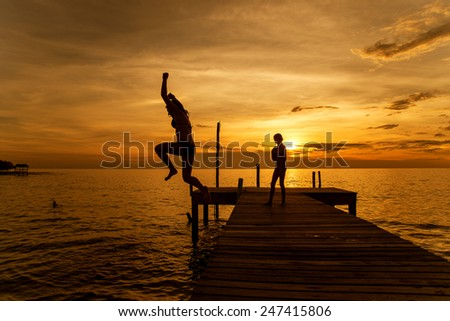 Silhouettes of woman jump into sea from pier - stock photo