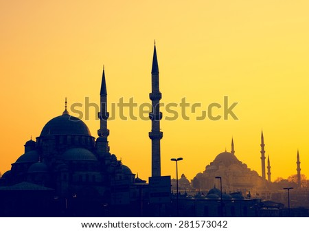 Silhouettes of Yeni Cami Mosque and Suleymaniye Mosque at sunset, soft light effect. Panoramic view of muslim architecture landmarks with minarets, district of Sultanahmet in old Istanbul. - stock photo