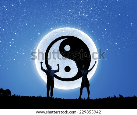 Silhouettes of young couple against yin yang sign
