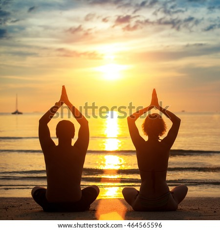 Silhouettes of young couple practicing yoga on the beach during sunset.