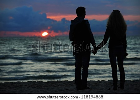 Silhouettes of young family romantic couple at sunset beach