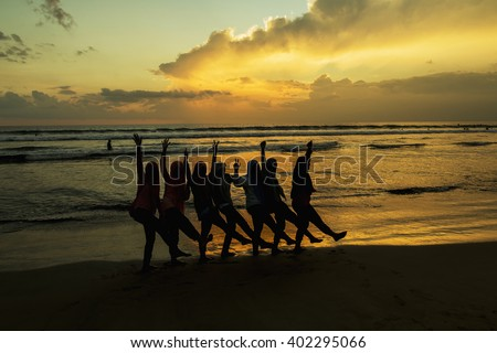 silhouettes of young girls at famous sunset beach in Kuta, Bali, Indonesia. - stock photo