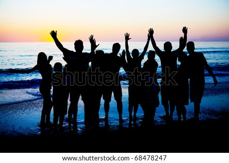 Silhouettes of young happy people enjoing sunset at the Florida beach. - stock photo