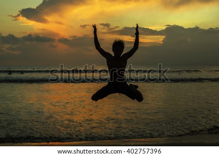silhouettes of young jumping boy at famous sunset beach in Kuta, Bali, Indonesia. - stock photo