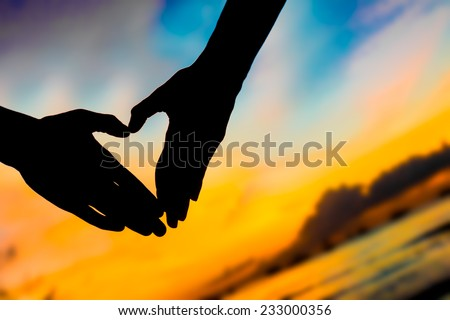 silhouettes of young loving couple on bright sunset sky and sea background making heart shape with their hands - stock photo