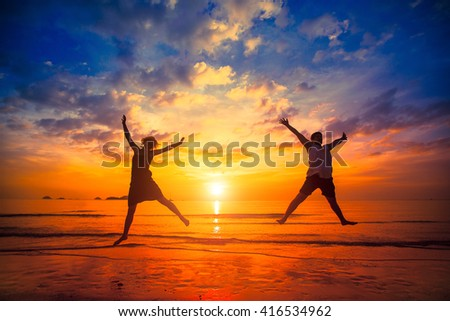 Silhouettes of young people jumping at sunset on the sea beach. - stock photo