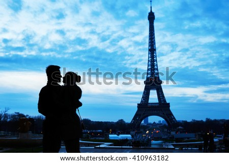 Silhouettes of young romantic couple near the Eiffel tower in Paris, France