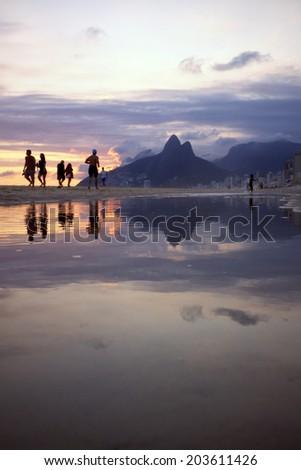 Silhouettes passing dusk sunset reflection of Rio de Janeiro Ipanema Beach Brazil with Two Brothers Dois Irmaos Mountain city skyline - stock photo