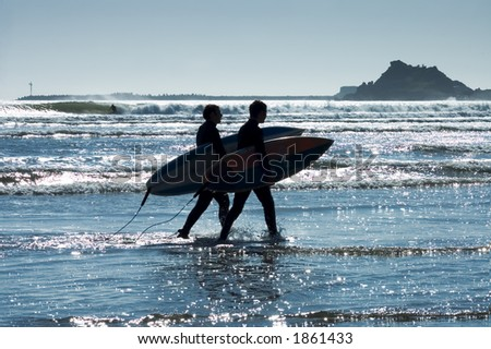 Silhouettes surfers at sunset on California beach going back home - stock photo