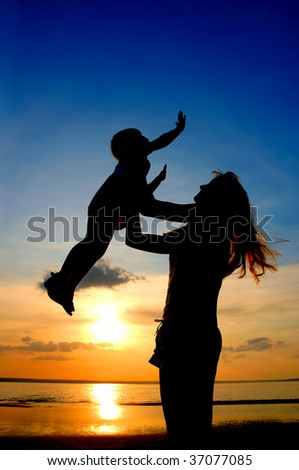 Silhouettes women and child on sundown - stock photo