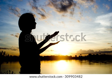 silhouettes Women praying hand over beautiful sun set background.