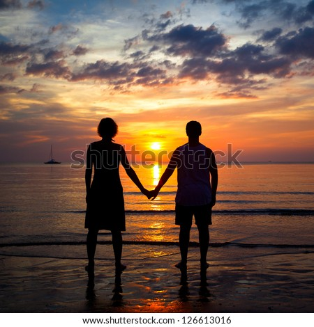 Silhouettes young couple on the beach at sunset, romantic picture - stock photo