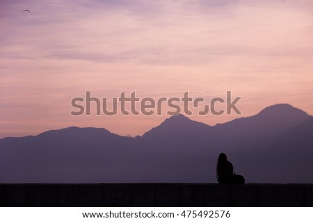 Silhoutte of a girl enjoying sunset, moutains background in Antalya, Turkey