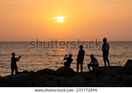 Silhoutte of a group of boys spending time together at the beach during a beautiful sunset - stock photo