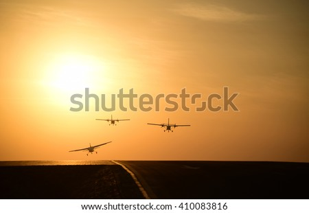 silhoutte of a group of three civilian aircraft or a small twin engine aeroplane taking off from the runway in a evening  sunset time with yellow orange sun and bright yellow sky in the background.