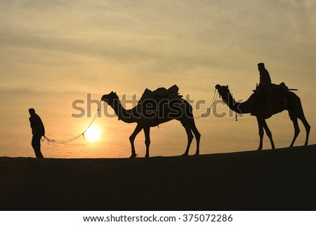 Silhoutte of Camel Trader in the Thar Desert during sunrise. Thar Desert located at Jaisalmer, Rajastan, India. - stock photo