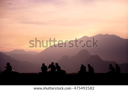 Silhouttes of people enjoying sunset, moutains background in Antalya, Turkey