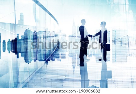 Silhouttes of Two Business People Having a Handshake - stock photo
