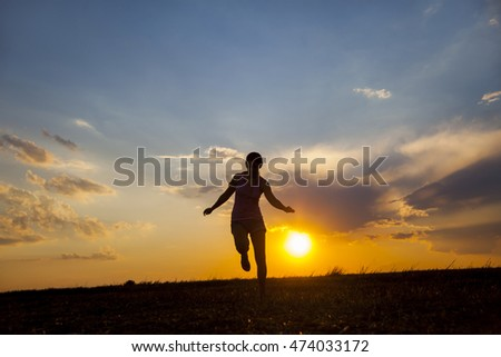 Silhuette of girl  in the field on the sunset backgroun