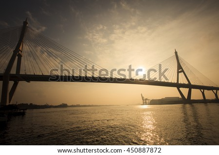 silhuoette photo of sun rising sky at bhumiphol bridge important transport and modern landmark crossing chaopraya river in samuthprakarn province out skirt bangkok thailand