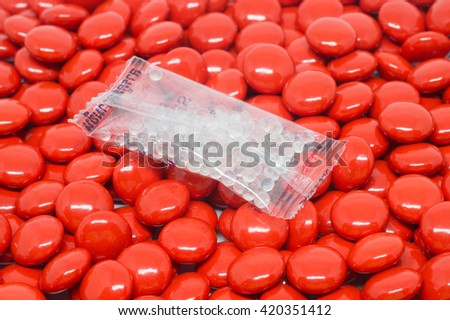 Silica gel in bag on red sugar coated pills tablets vitamin - stock photo