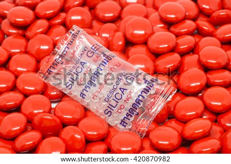 "Silica gel in bag that labeled ""Do not eat"" in Thai and English on red sugar coated pills tablets vitamin - stock photo"