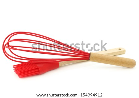 silicon egg beater and brush with wooden handle on a white background - stock photo