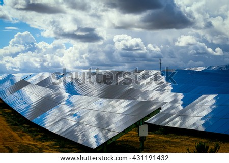Silicon panels of solar batteries against the cloudy sky in the middle of the day. - stock photo
