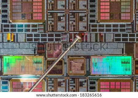 Silicon wafer with printed electronic circuit compared to a needle - stock photo