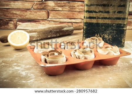 Silicone form with homemade pastries, a rolling pin, a jar of flour, half a lemon and an apple on a light wooden table. Toned. - stock photo