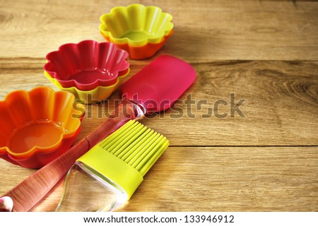 Silicone whisk, spatula, brush and cupcake liners on wooden table - stock photo
