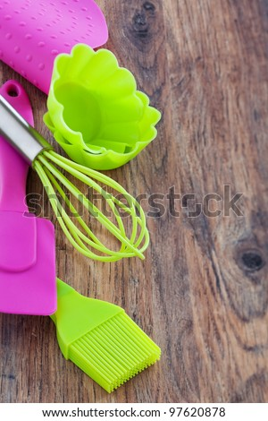 Silicone whisk, spatula, brush and cupcake liners on wooden table, selective focus - stock photo