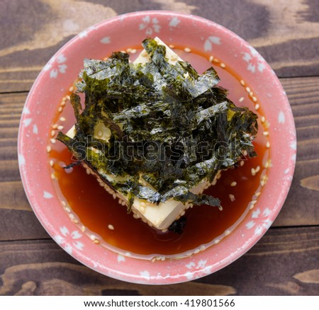 Silken tofu with gochujang and sesame oil decorate, cold bean curd, soybean with seaweed in bowl on wooden background - stock photo