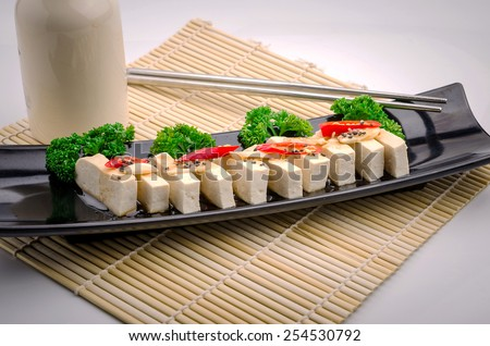 Silken tofu with gochujang and sesame oil decorate with spring onion and ginger - stock photo