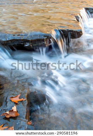 Silky brook water running  on flat rocks.  - stock photo