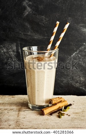 Silky dairy drink in tall glass with two swirl colored straws on a long rustic table with a sprinkle of cinnamon - stock photo